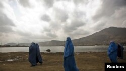 Burqa-clad women walk along a road in Kabul, where women continue to struggle for their rights.