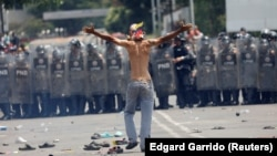 Після сутичок на кордоні Венесуели (позаду, за лавами венесуельської поліції) і Колумбії, з якої йде прихильник венесуельської опозиції, фото 23 лютого 2019 року