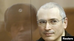 Mikhail Khodorkovsky stands in the defendants' cage before the start of a court session in Moscow on December 28.