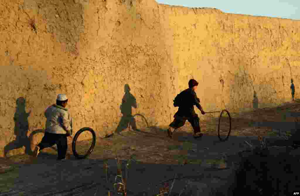 Afghan boys play with a tire outside their house in the Zhari district of Kandahar Province. (AFP/Javed Tanveer)