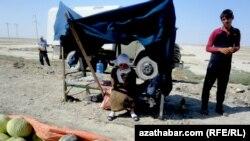 Түркіменстан Ашхабат маңында жол бойында қауын сатып тұрған адамдар.