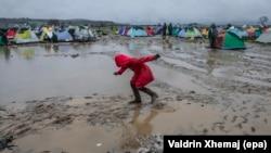 Një vajzë refugjate ecë nëpër baltë në një kamp refugjatësh
