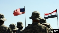 US troops stand to attention in front of American and Iraqi (R) flag. May 15, 2020