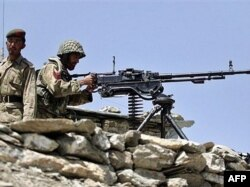 FILE: A Pakistani Army soldiers take position at Sholam Post, a military checkpost overlooking Wana, South Waziristan