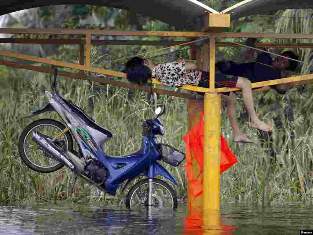 Thais pass the time next to a motorbike hanging from the beams of a bus stop above a flooded road in Pathum Thani province, on the outskirts of Bangkok. (Damir Sagolj for Reuters)