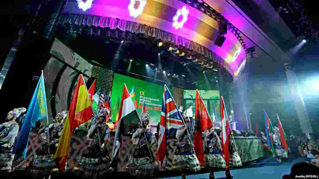 Performers hold the flags of the 27 countries participating in the festival.