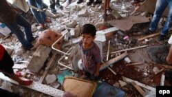Палестинці дивляться на розбомблену класну кімнату у школі ООН, Смуга Гази, 30 липня 2014