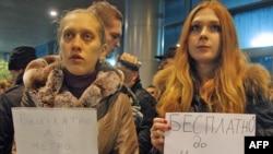 """""""NASHI"""" harakati a'zolari """"Domodedovo"""" aeroportida """"metrogacha bepul eltib qo'yamiz"""" yozuvli plakatlar bilan."""