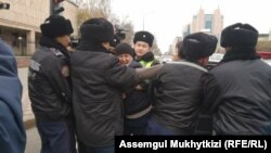 kazakh activist Dulat Aghadil (center) being detained by police in Nur-Sultan on October 26.