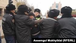 Полицейлер белсенді Дулат Ағаділді (ортада) күштеп ұстап жатқан сәт. Нұр-Сұлтан, 26 қазан 2019 жыл.