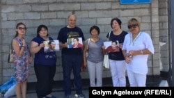 Сторонники Ермека Нарымбаева стоят с его фотографиями перед зданием тюрьмы для административно осужденных в Алматы, куда он заключен на 15 суток. 6 июля 2015 года.