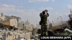 یک سرباز سوری بر ویرانههای مرکز تحقیقاتی سوریه در منطقه برزه در شمال دمشق