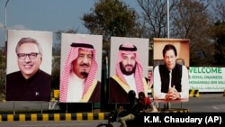 Pakistani riders drive past portraits of Pakistani and Saudi leaders display on the occasion of the visit by Saudi Arabia's Crown Prince to Pakistan.