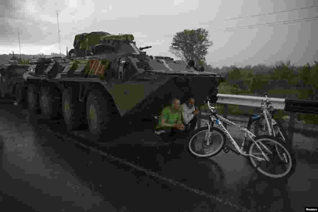 Ukrainian civilians find cover from the rain under a Ukrainian Army armored personnel carrier at a checkpoint near the town of Slovyansk on May 2. (Reuters/Baz Ratner )