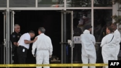 Investigators at a movie theater in Colorado where a gunmen went on the rampage, killing 12 people.