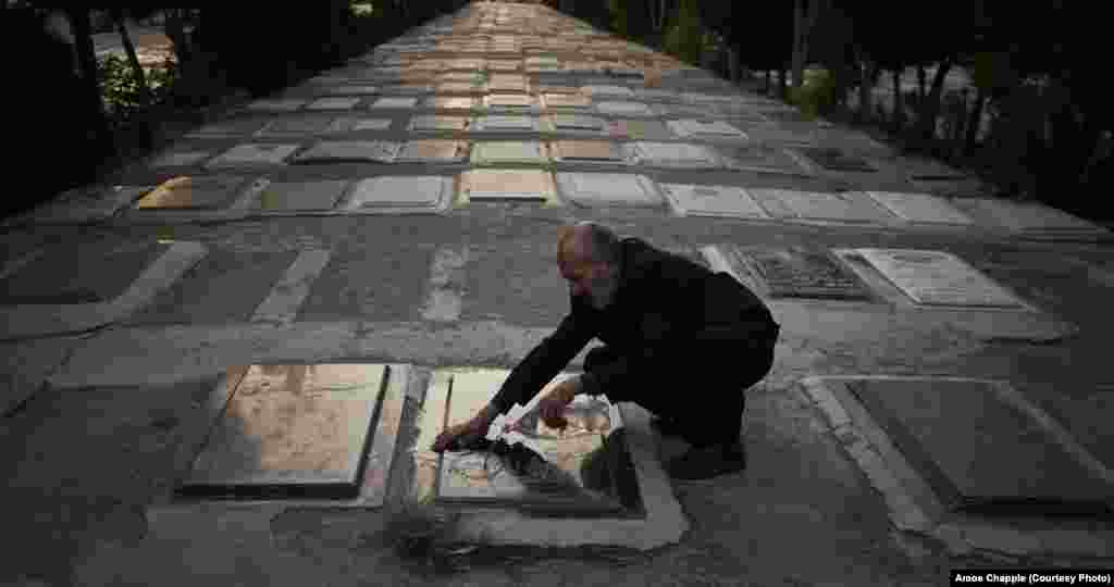 A man washes a gravestone at the Behesht-e Zahra cemetery in Tehran, dedicated to some 200,000 victims of the Iran-Iraq war. At times, fountains at the cemetery have been filled with red dye to represent the blood of martyrs.