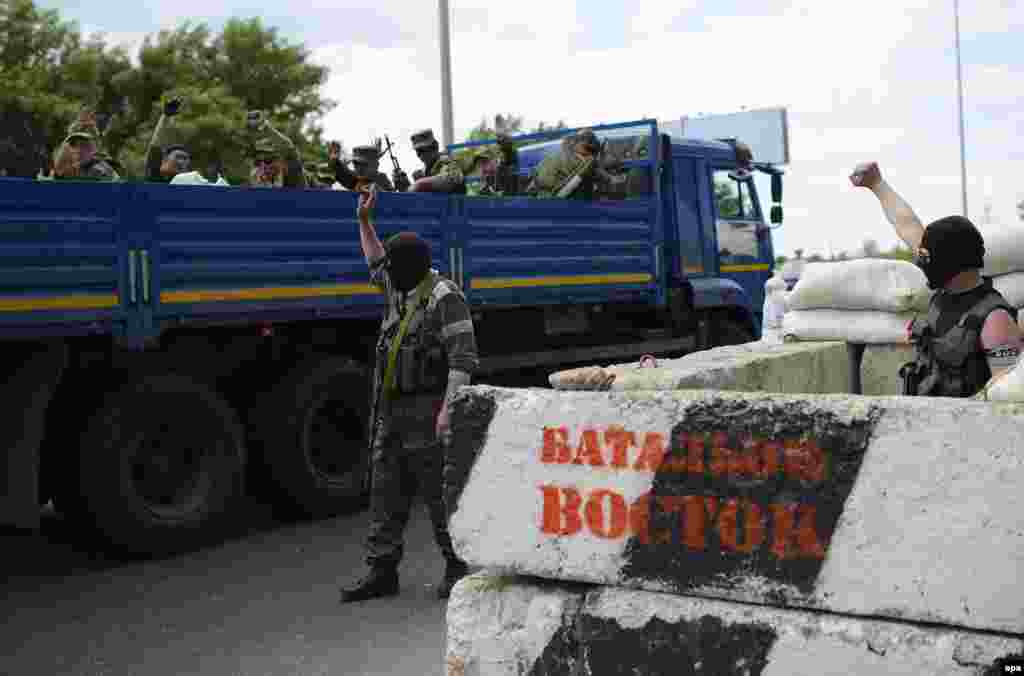 "Pro-Russian separatists said to be from the self-proclaimed ""Vostok Battalion"" cheered on their comrades aboard a truck at a checkpoint on the outskirts of Donetsk on election day, one day before the airport fighting."