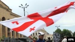 Грузинський хлопчик з державним прапором на вулицях Тбілісі