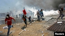 Stambul şäheriniň Taksim meýdançasynda polisiýa protestçileri dargatmak üçin göz ýaşardyjy gazlary ulanýar. Stambul, 12-nji iýun, 2013.