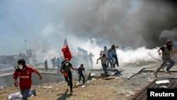 Участники акций протеста бегут от струй слезоточивого газа, используемого полицией. Площадь Таксим, Стамбул, 11 июня 2013 года.