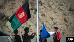 Afghan National Army soldiers raise their national flag next to the French flag during a transition ceremony at a base in Afghanistan in April.