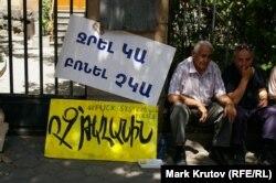 """Лозунги протестующих: """"Можете поливать нас, но не арестовывайте!"""" (вверху), """"Нет грабежу!"""" (внизу)"""