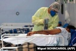 Родственник посещает пациента в импровизированной больнице, организованной в спортзале в Сан-Паулу