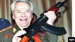 Михаил Калашников АК-47 автоматын ұстап тұр.