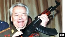 "Arms designer General Mikhail Kalashnikov holds his iconic ""Kalashnikov"" assault rifle during celebrations in 1997 of the 50th anniversary of the first-version AK-47."
