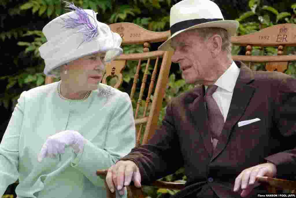 În acest fotografie făcută la 17 iulie 2002 regina britanică Elisabeta a II-a și prințul britanic Philip, ducele de Edinburgh discutau în timp ce erau așezați în timpul unei reprezentații muzicale în grădinile Abbey, Bury St Edmunds.