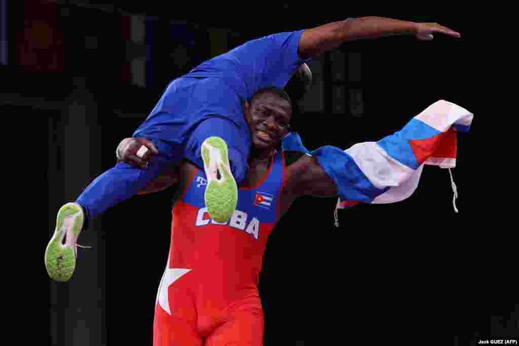 Cuba's Mijain Lopez Nunez carries his coach as celebrating his gold medal win against Georgia's Iakobi Kajaia in their men's greco-roman 130kg wrestling final match during the Tokyo 2020 Olympic Games at the Makuhari Messe in Tokyo on August 2, 2021.