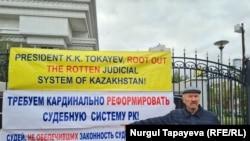 Активист Ильшат Кензин указывает на баннеры на ограждении у здания Верховного суда. Нур-Султан, 21 сентября 2021 года
