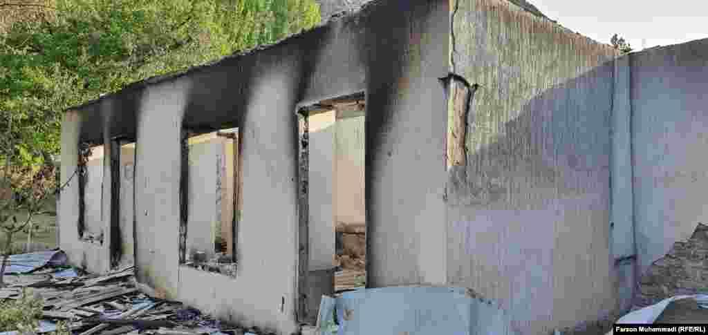 Сожженное в результате обстрелов здание в селе Сомониен в Таджикистане