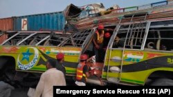Rescuers work at the site of a bus accident near Dera Ghazi Khan in Punjab Province on July 19.
