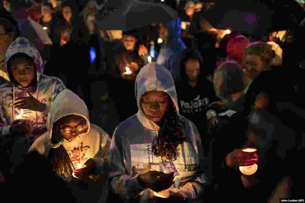 People hold candles during a vigil for the centennial commemorations of the Tulsa Race Massacre in the historic Greenwood neighborhood, late Monday, May 31, 2021, in Tulsa, Oklahoma. President Joe Biden is expected to visit Tulsa later on Tuesday June 1, after declaring Monday May 31 a day of remembrance.