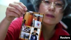 Li Na Dzsum szöuli otthonában fényképeket mutat a fiáról a Reuters munkatársának