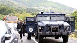 KOSOVO -- Kosovo special police with armored vehicles stand on the road near the northern Kosovo border crossing of Jarinje, September 20, 2021