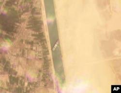 Műholdkép a Szuezi-csatornában átlósan zátonyra futott Ever Given hajóról, 2021. március 23-án.