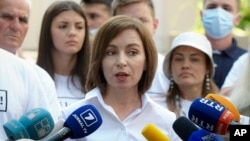 Moldovan President Maia Sandu speaks to reporters in Chisinau after casting her vote in the country's snap parliamentary elections.