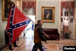 Një protestues mban flamurin e Konfederatës, pasi ka hyrë në Kongresin amerikan. Uashington, 6 janar, 2021.