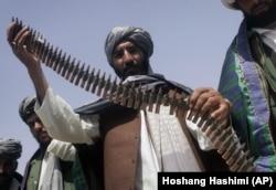 Un fost taliban ține o centură de muniție în timpul unei ceremonii de predare a armelor din Herat, Afganistan, 26 aprilie 2012. Aproximativ 10 foști talibani din provincia Herat și-au predat armele în cadrul unui program de reconciliere a păcii.