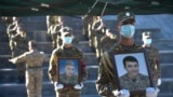 ARMENIA -- Servicemen hold portraits of soldiers Vazgen Aslanyan and Abraham Sargyan, who were killed in the fighting between Armenia and Azerbaijan over the breakaway region of Nagorno-Karabakh, during a funeral ceremony at Yerablur military pantheon in