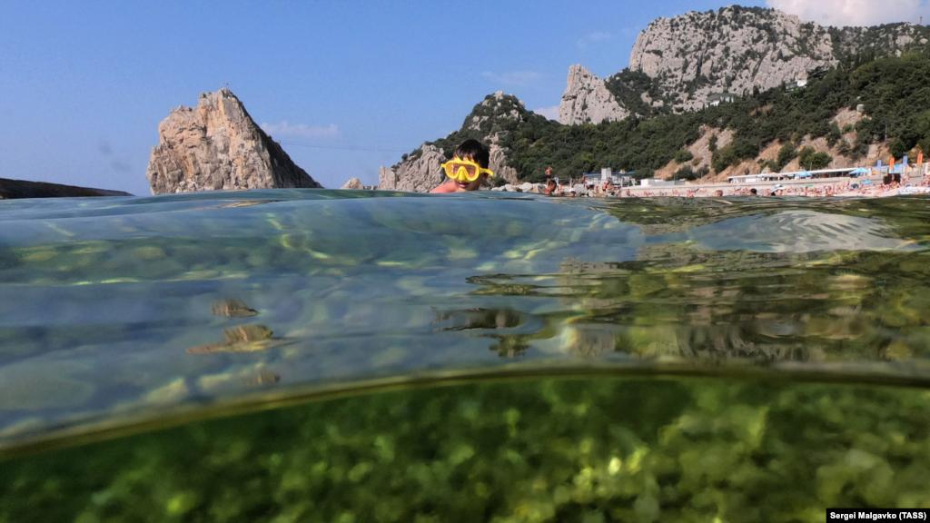 Хлопчик у масці для підводного плавання пірнає в Чорне море в околицях курортного селища Сімеїз, серпень 2021 року