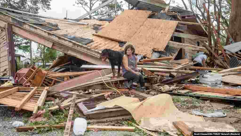 Fran Tribe sjedi sa psom ispred kuće uništene u uragana, Houma, Louisiana.