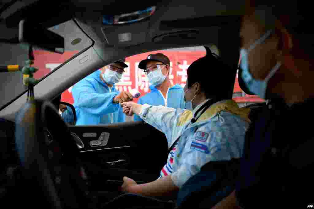 Співробітники безпеки в захисних костюмах перевіряють температуру людей, які виїжджають з ринку Сінфаді в Пекіні, Китай