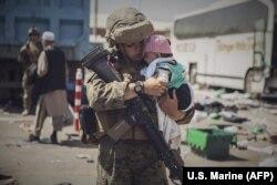 Un militar din SUA ține în brațe un copil pe măsură ce familia trece prin Centrul de Control al Evacuării (ECC). 28 august 2021