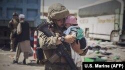 Кабул эл аралык аэропортундагы АКШ аскери ата-энеси текшерүүдөн өтүп жаткан баланы сооротууда. 30-август, 2021-жыл.