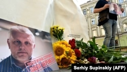 A man holds journalist Pavel Sheremet's portrait at his memorial on the site where Sheremet's car exploded five years before in Kyiv on July 20.