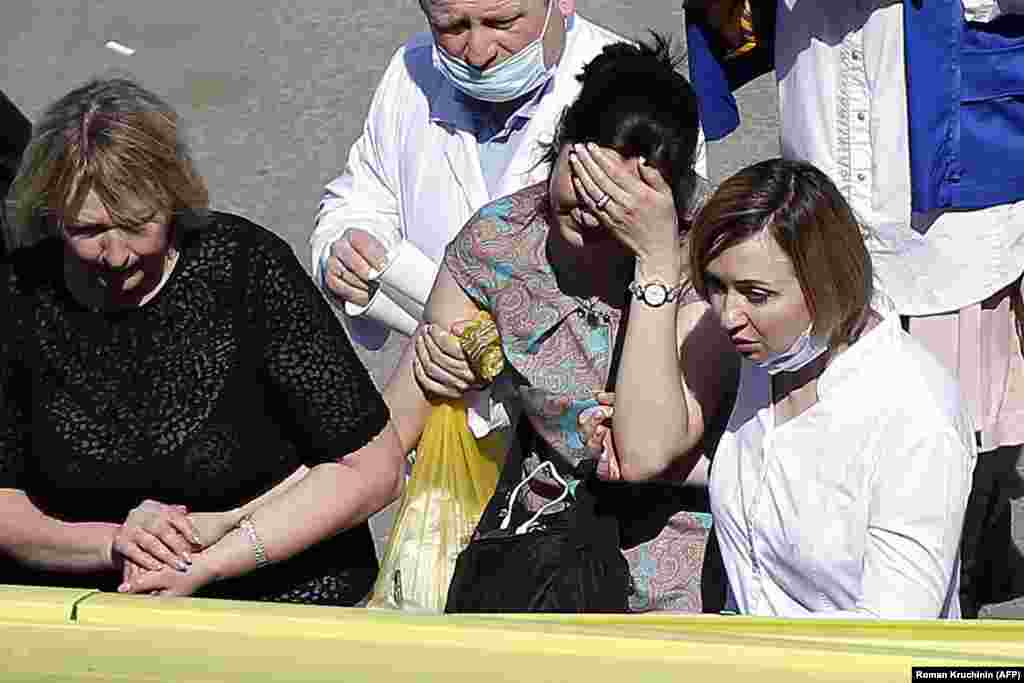 A woman cries as she is taken to an ambulance at the scene of the shooting at School No. 175 in Kazan.
