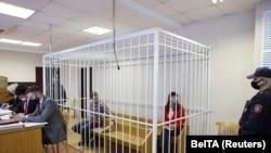 Кацярына Барысевіч і Арцём Сарокін за кратамі ў судовай залі. Менск, 19 лютага.